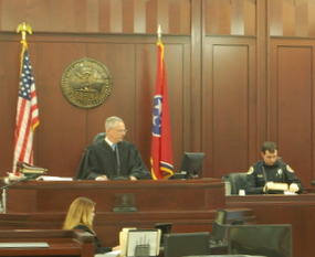 Officer Charles Cole walks the courtroom through the evidence collected from Wayne Mills' person at Vanderbilt Hospital.